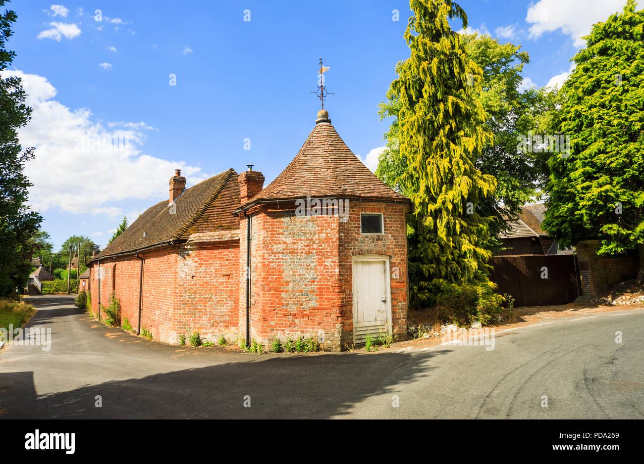 Old brick stables building in Little Bedwyn, a small rural village in Wiltshire, southern England in summer - Stock Image