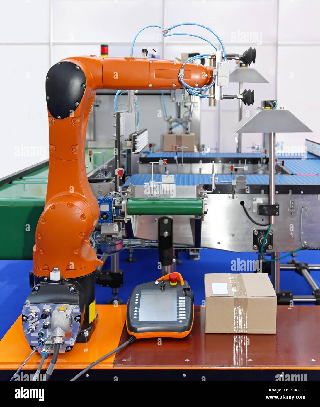 Articulated robot at packaging line in factory - Stock Image