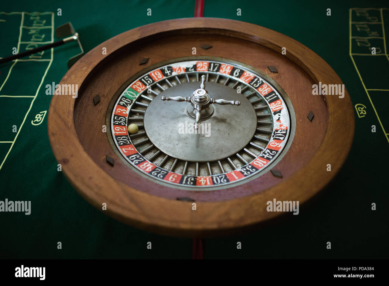 Roulette wheel with the winning ball on red twelve - Stock Image