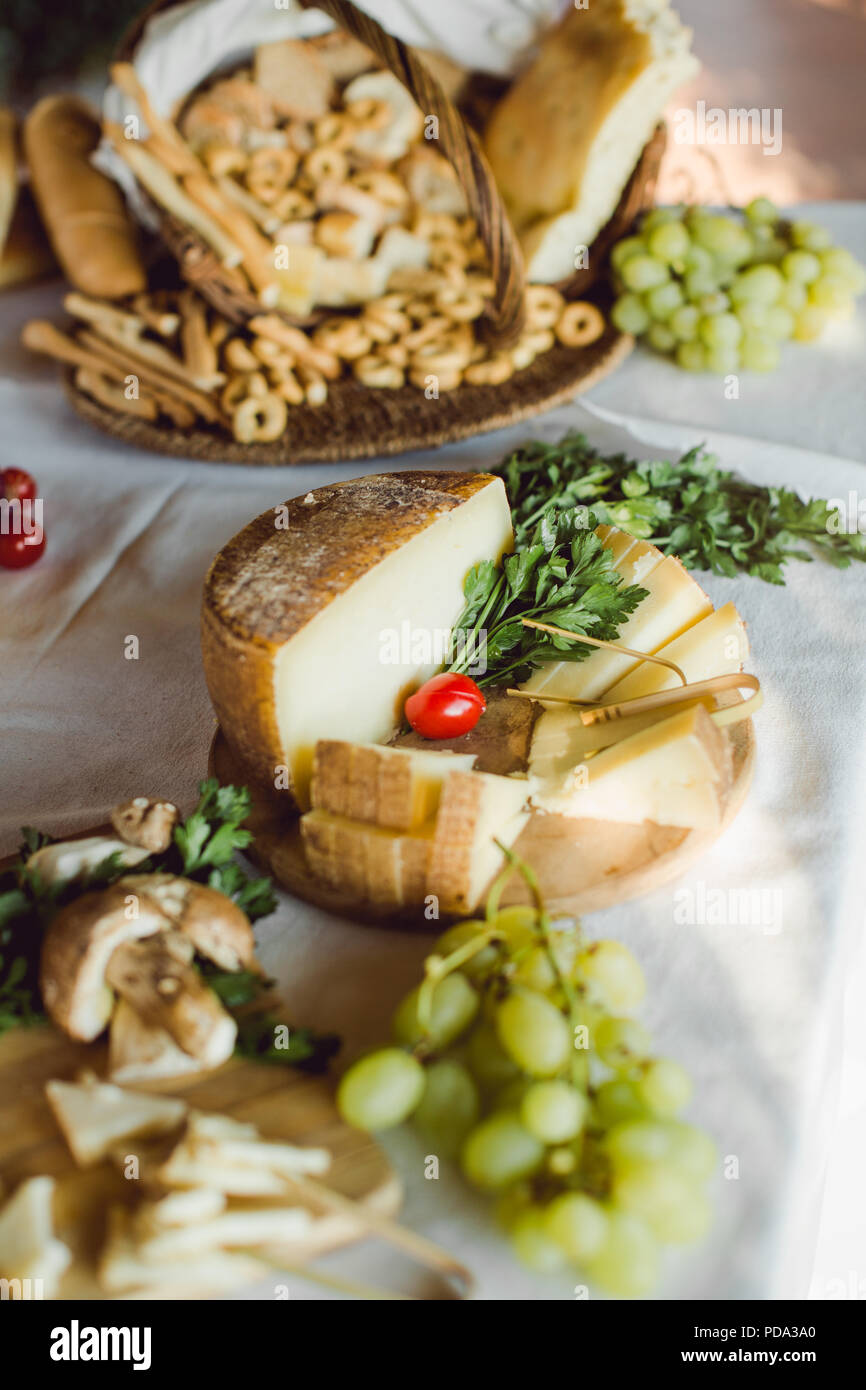 Traditional Italian hard cheese sliced and ready to eat at an Italian buffet - Stock Image