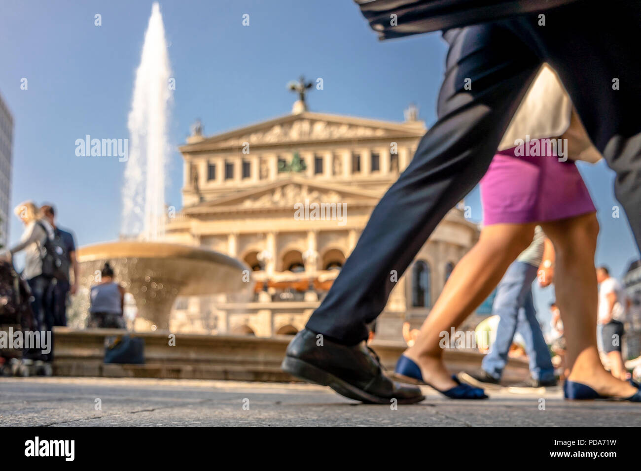 Blurry shot of people walking on the Opernplatz in Frankfurt Germany and looking for refreshment in the water of the fountain. - Stock Image