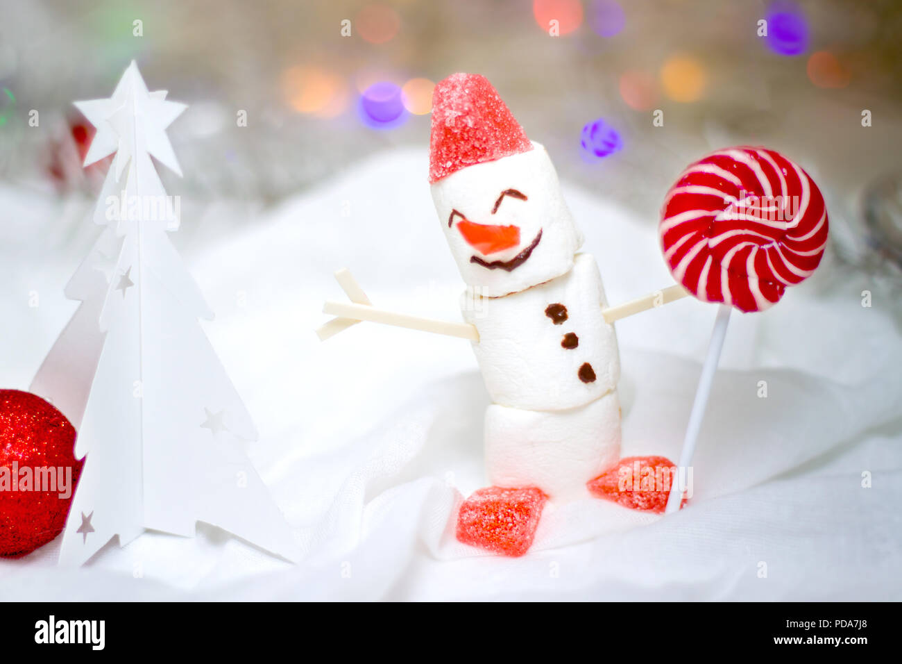 holidays winter and celebration concept christmas and new year card with snowman from marshmallow and red lollipop and a white christmas tree made