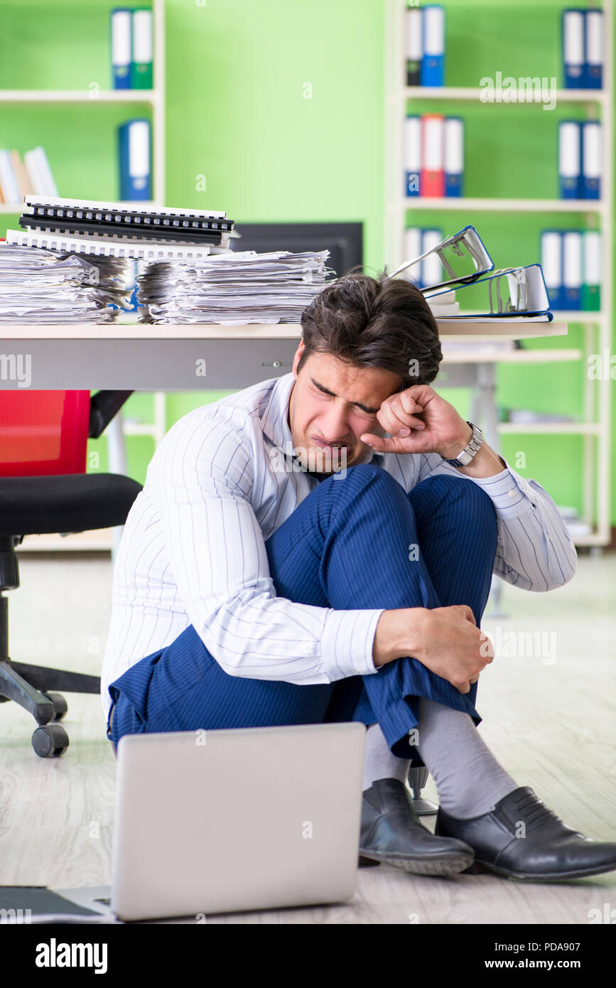 Frustrated businessman stressed from excessive work - Stock Image