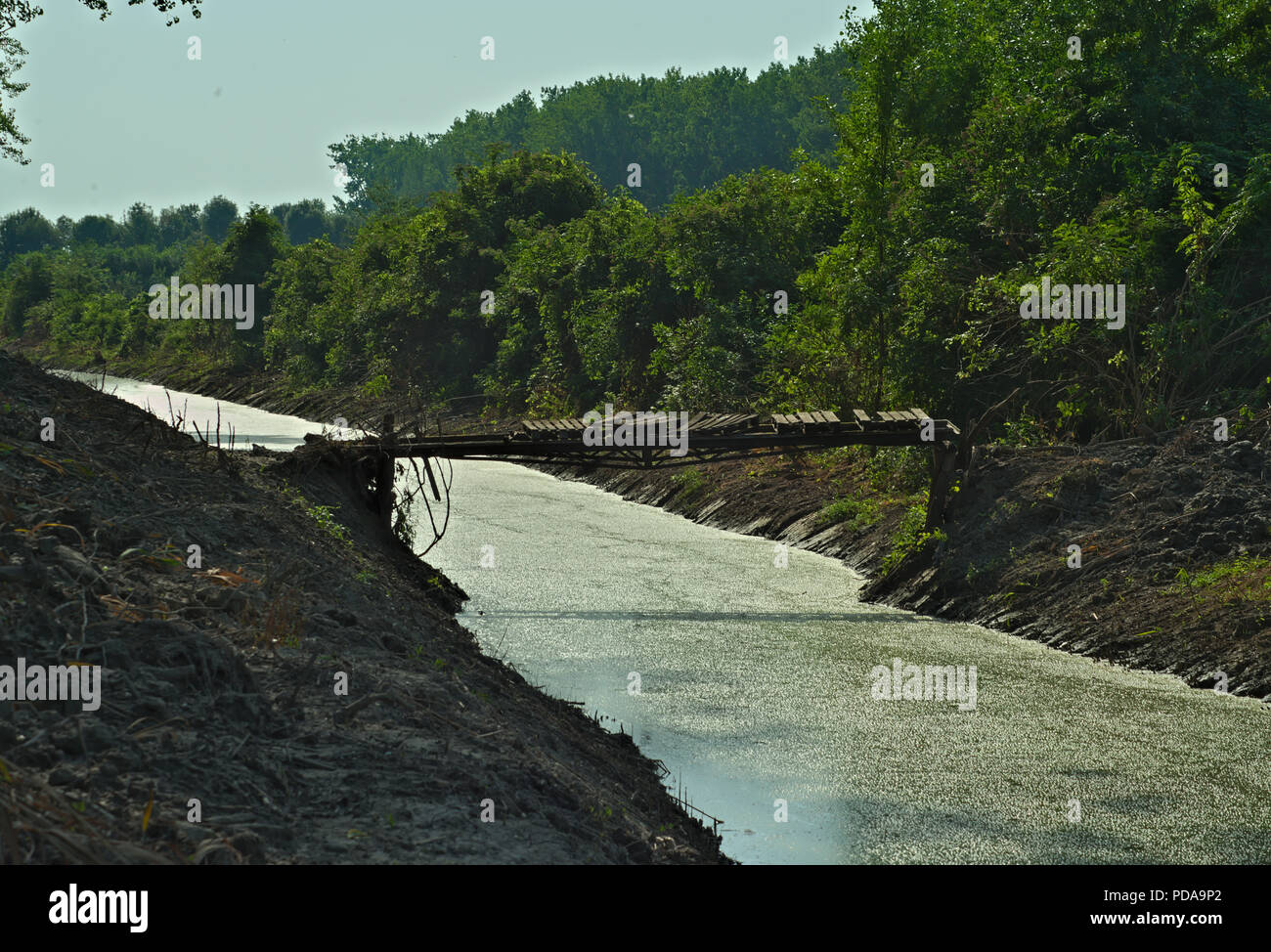 Rustic and dangerous bridge over small river - Stock Image