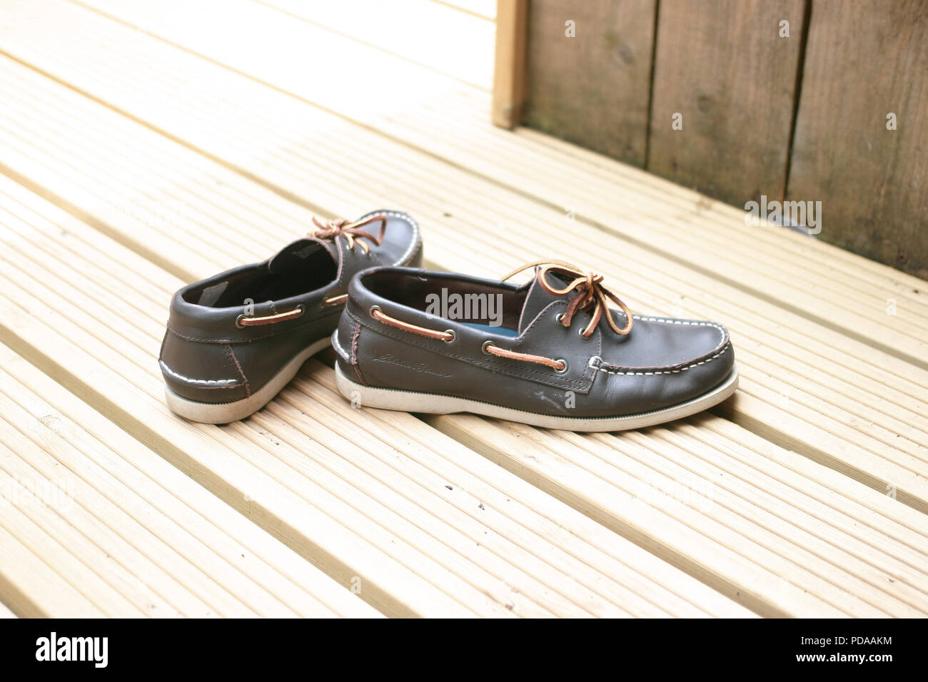 A pair of Men's leather shoes, on wooden decking outside in the garden. Stock Photo