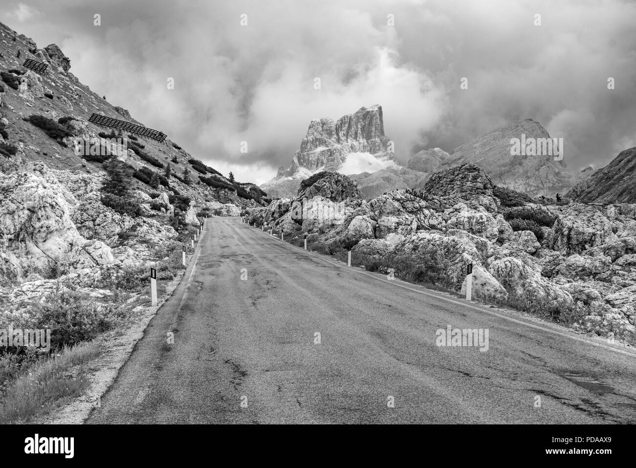 Empty deserted road in black and white leading to menacing stormy, cloudy mountains in the Dolomites, Italy - Stock Image