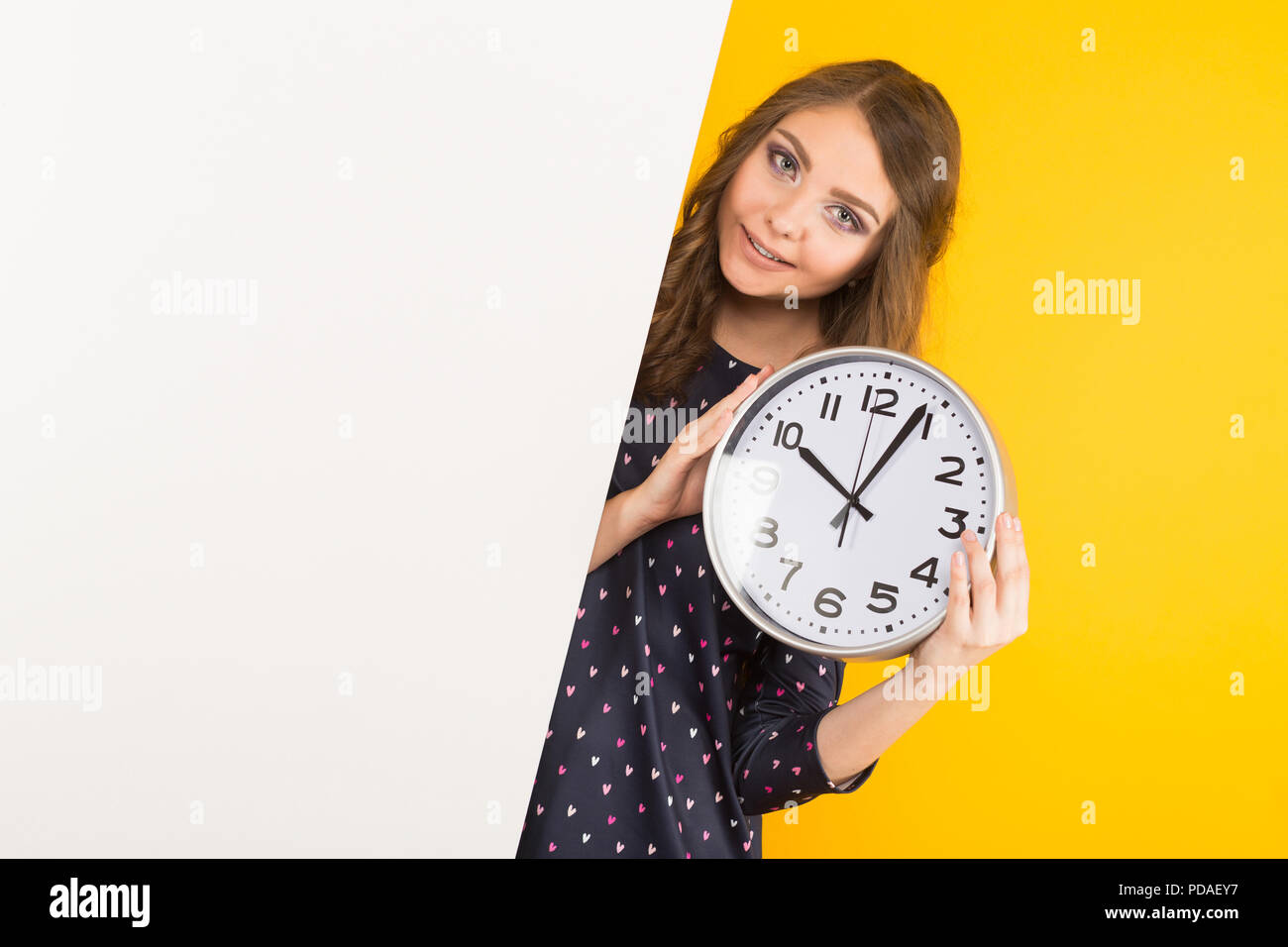 Brunette woman with clocks and blank banner Stock Photo
