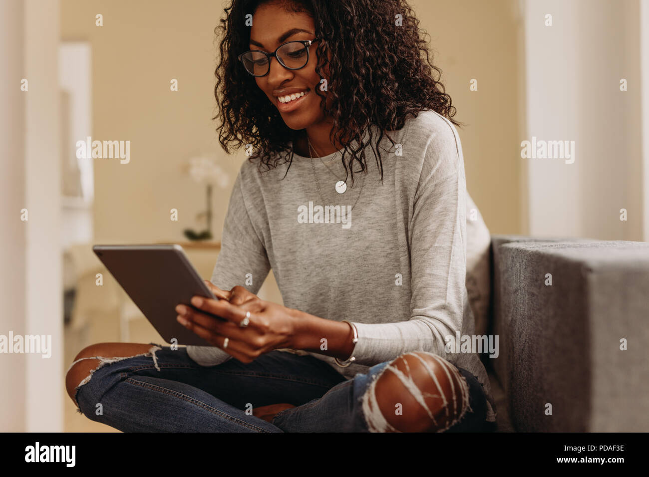 Woman sitting on sofa at home working on tablet pc. Smiling woman using a tablet pc while sitting at home with legs crossed. - Stock Image