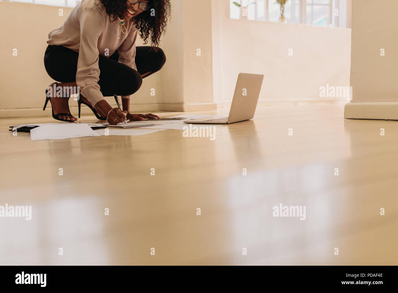 Woman entrepreneur in formal attire making notes while working on laptop computer at home. Businesswoman sitting on floor wearing sandals at home maki - Stock Image