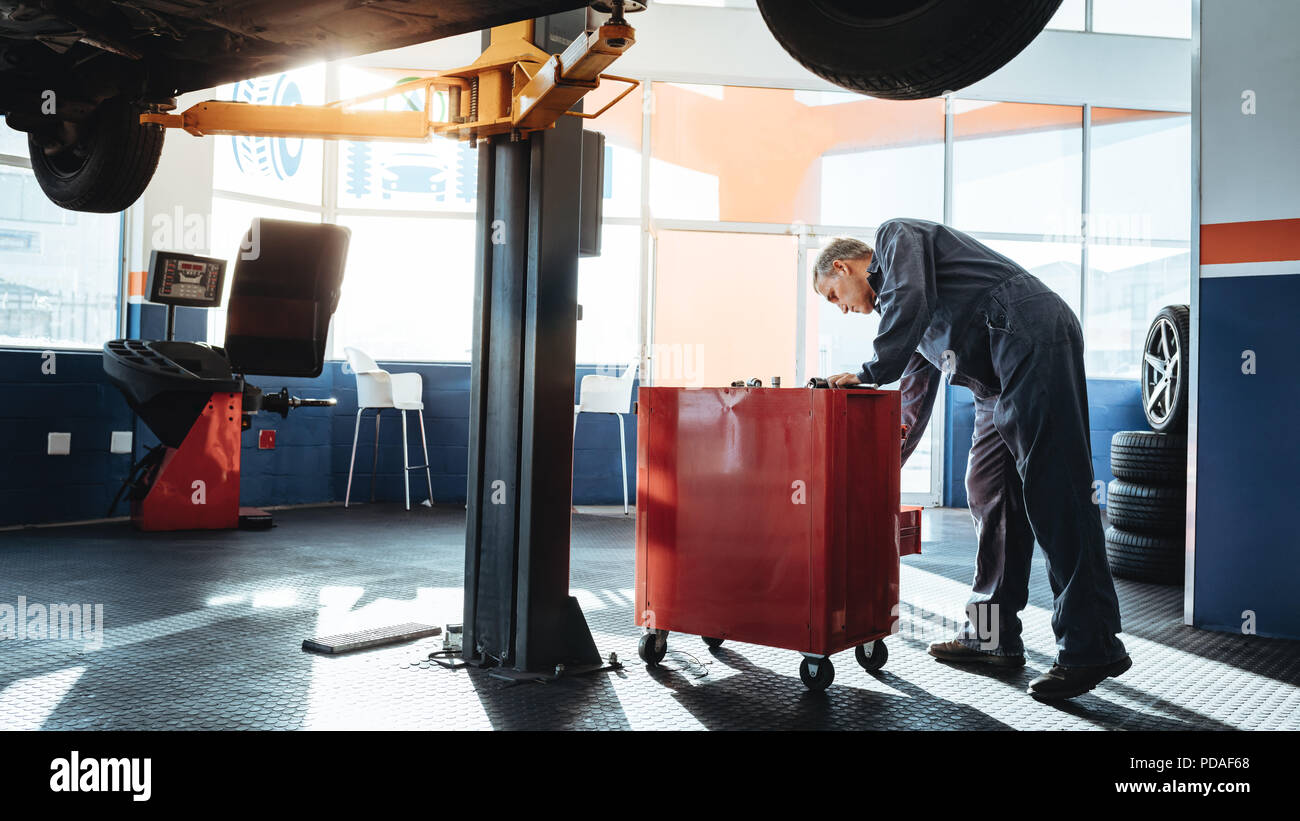 Mechanic working in the garage and looking for tools in toolbox. Repairmen working in service station. - Stock Image