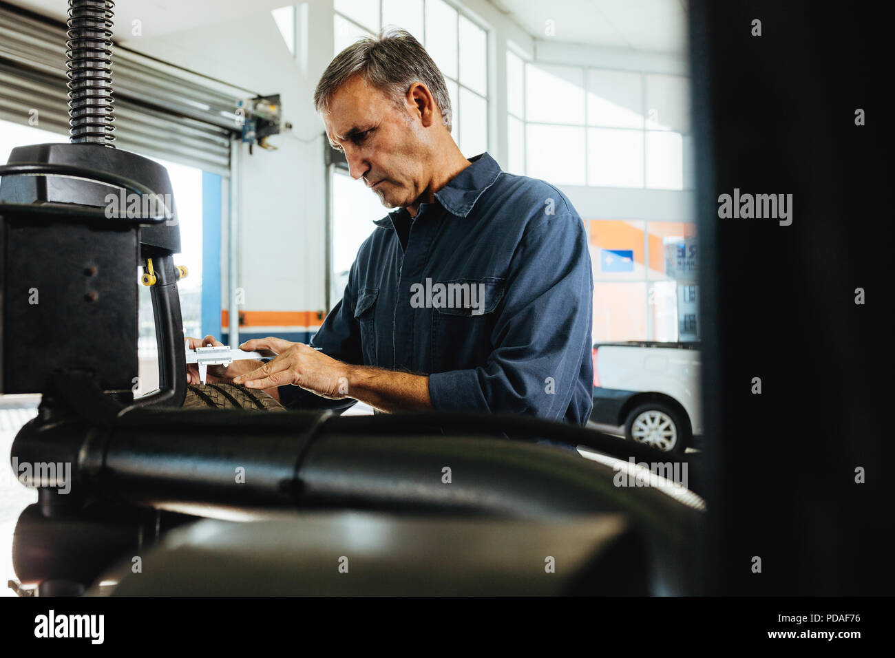 Mechanic checking the car wheel surface on machine. Technician working in automobile tyre mounted on machine in garage. Stock Photo