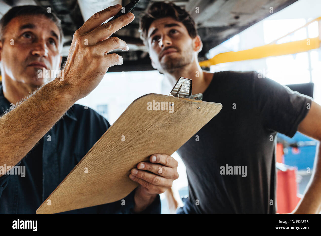 Two experienced mechanics standing under a car and inspecting the problem. Mechanics doing car inspection with clipboard. - Stock Image