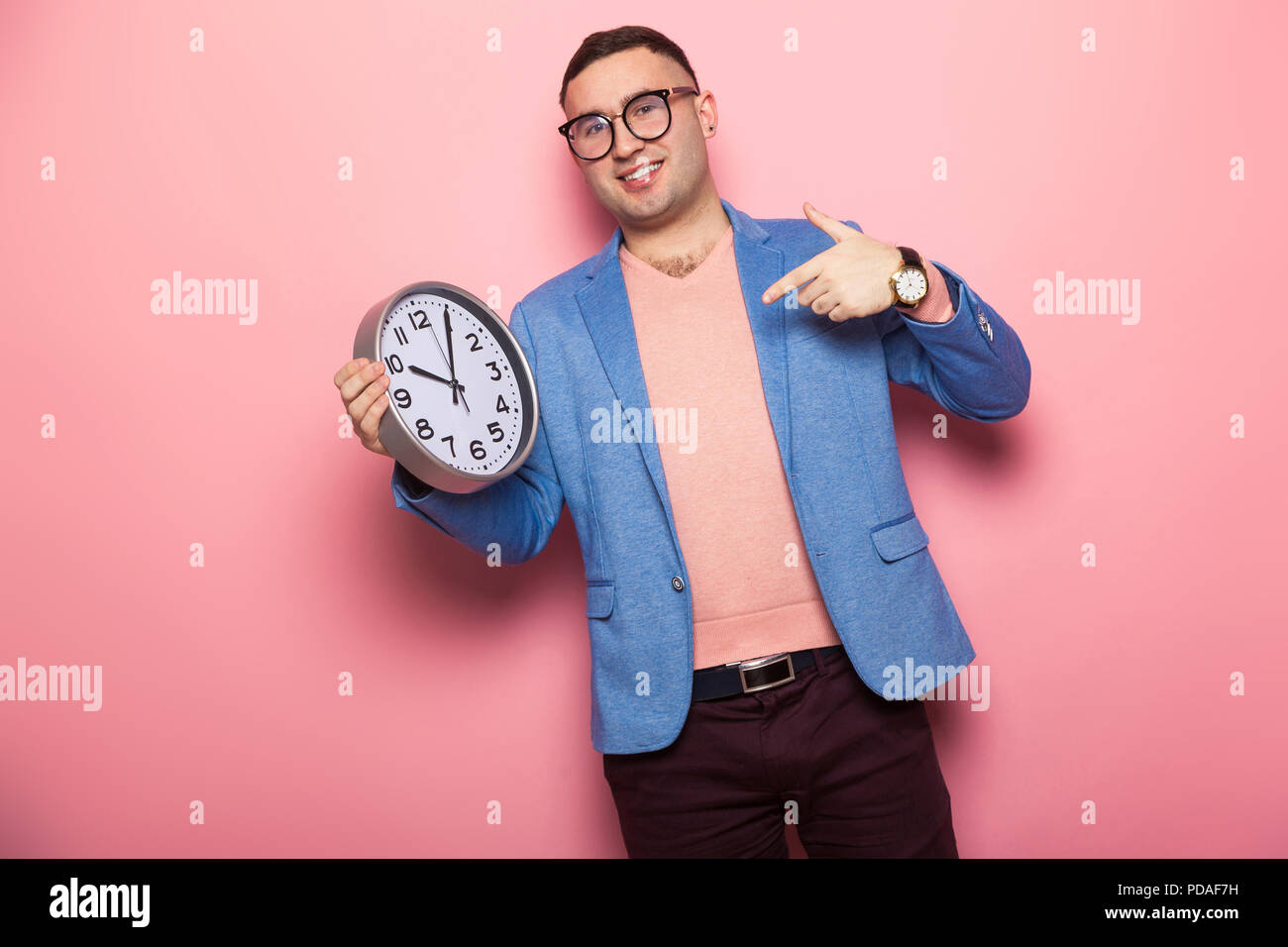 Handsome man in bright jacket with clocks - Stock Image
