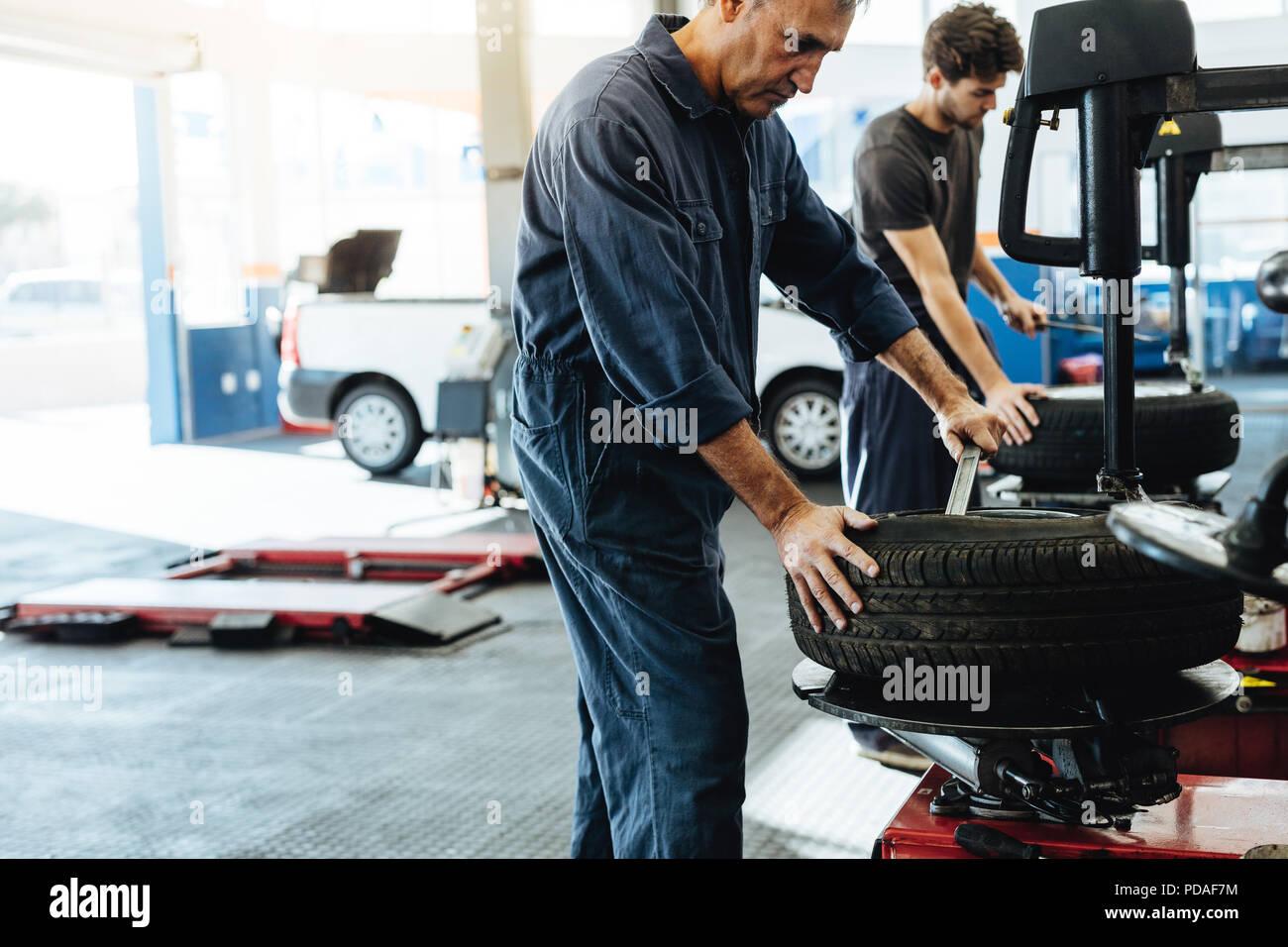 Mechanics working in car repair workshop. Auto repair workers working on tire replacing machine in auto repair shop. - Stock Image