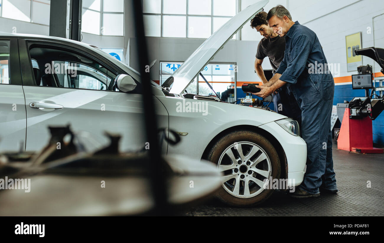 Automobile technicians using electronic diagnostic equipment to tune a car. Mechanics using a device to check the engine. - Stock Image