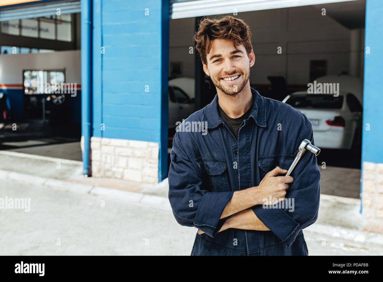 Professional auto mechanic in uniform with wrench. Young mechanic standing with his arms crossed outside his garage. - Stock Image