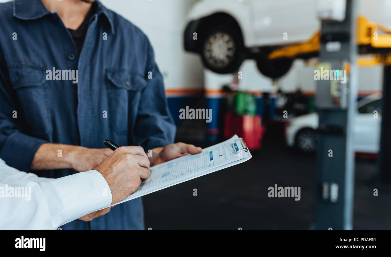 Mechanic taking sign on document from customer in garage. Hands of car service client signing papers after getting his car repaired. Stock Photo