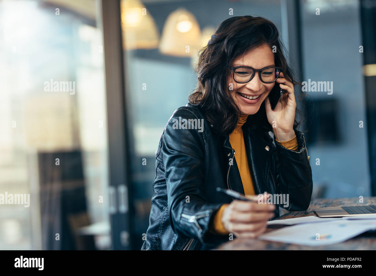 Businesswoman in casuals sitting at office on a table talking over mobile phone. Woman entrepreneur managing her business. - Stock Image