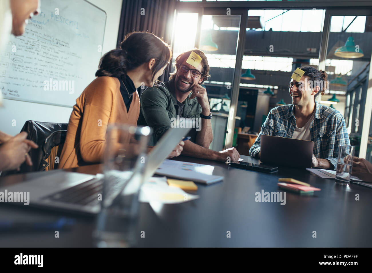 Business team sitting around a table in office lobby with sticky notes on their forehead having a brainstorming meeting. Corporate business people sit - Stock Image