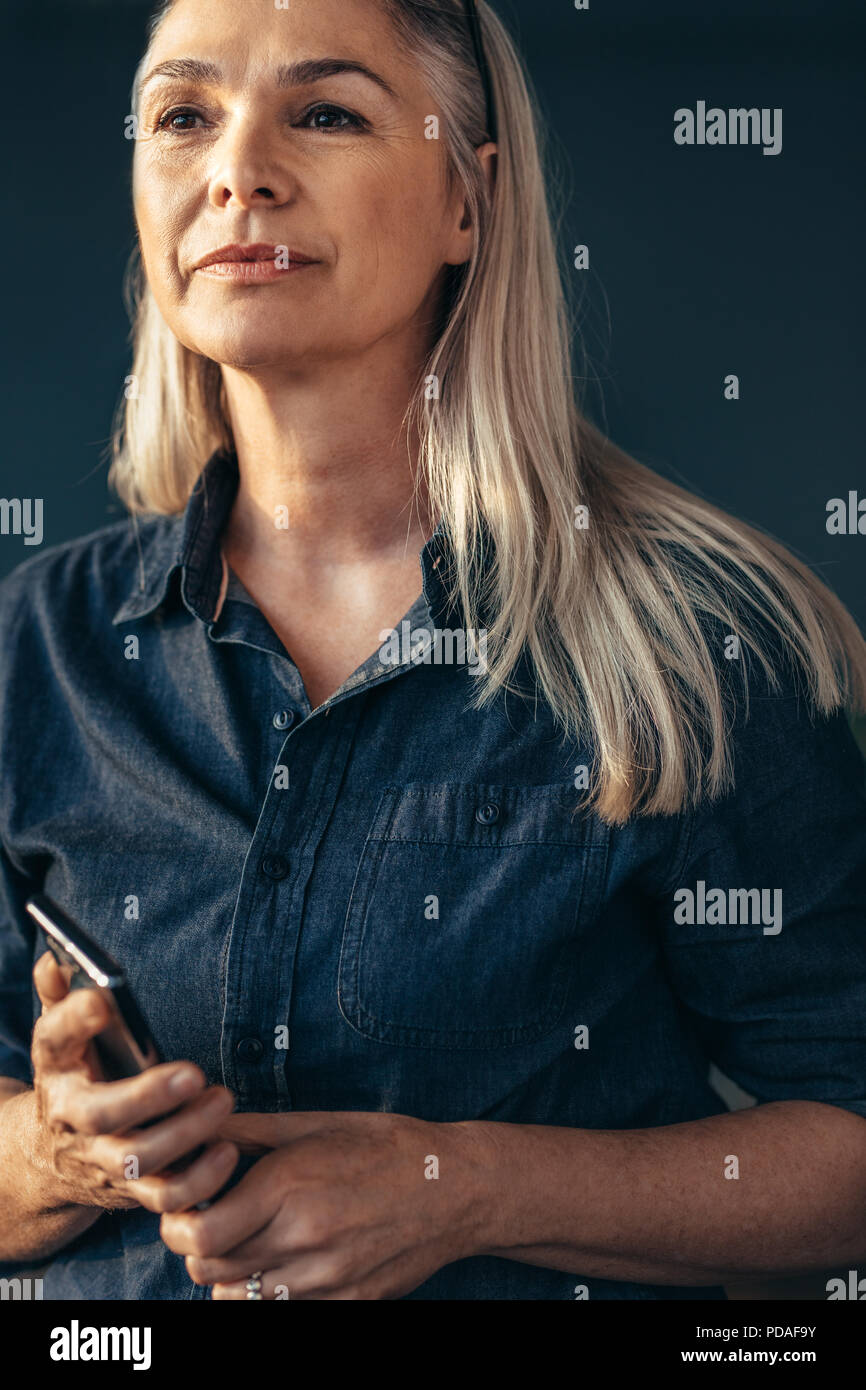 Portrait of confident senior woman holding phone looking away. Woman with white hair in casuals. - Stock Image