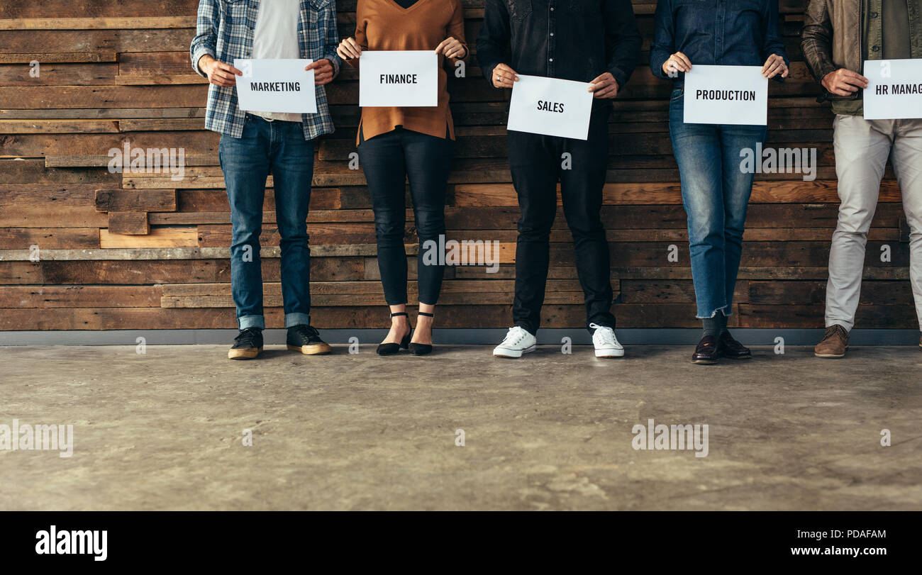 Low section of business people standing in row against a wall holding names of their respective departments on a placard. Candidates shortlisted of an - Stock Image