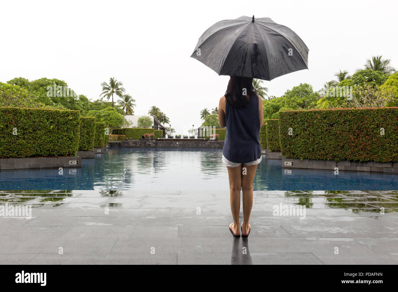 Woman with umbrella standing by swimming pool watching the rain  - Stock Image