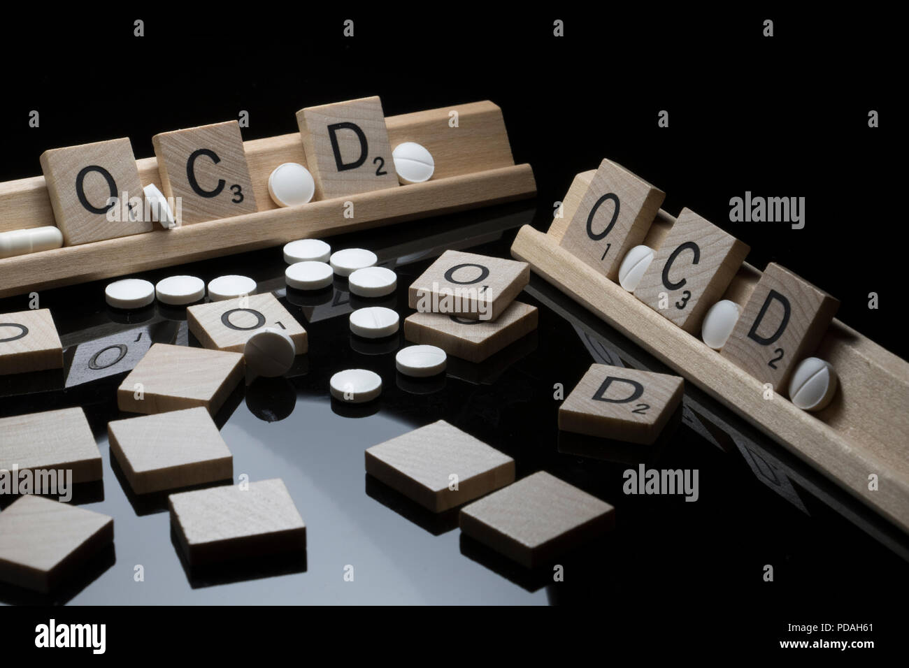 Scrabble letters spelling OCD with white prescription pills. Mental health awareness concept. - Stock Image