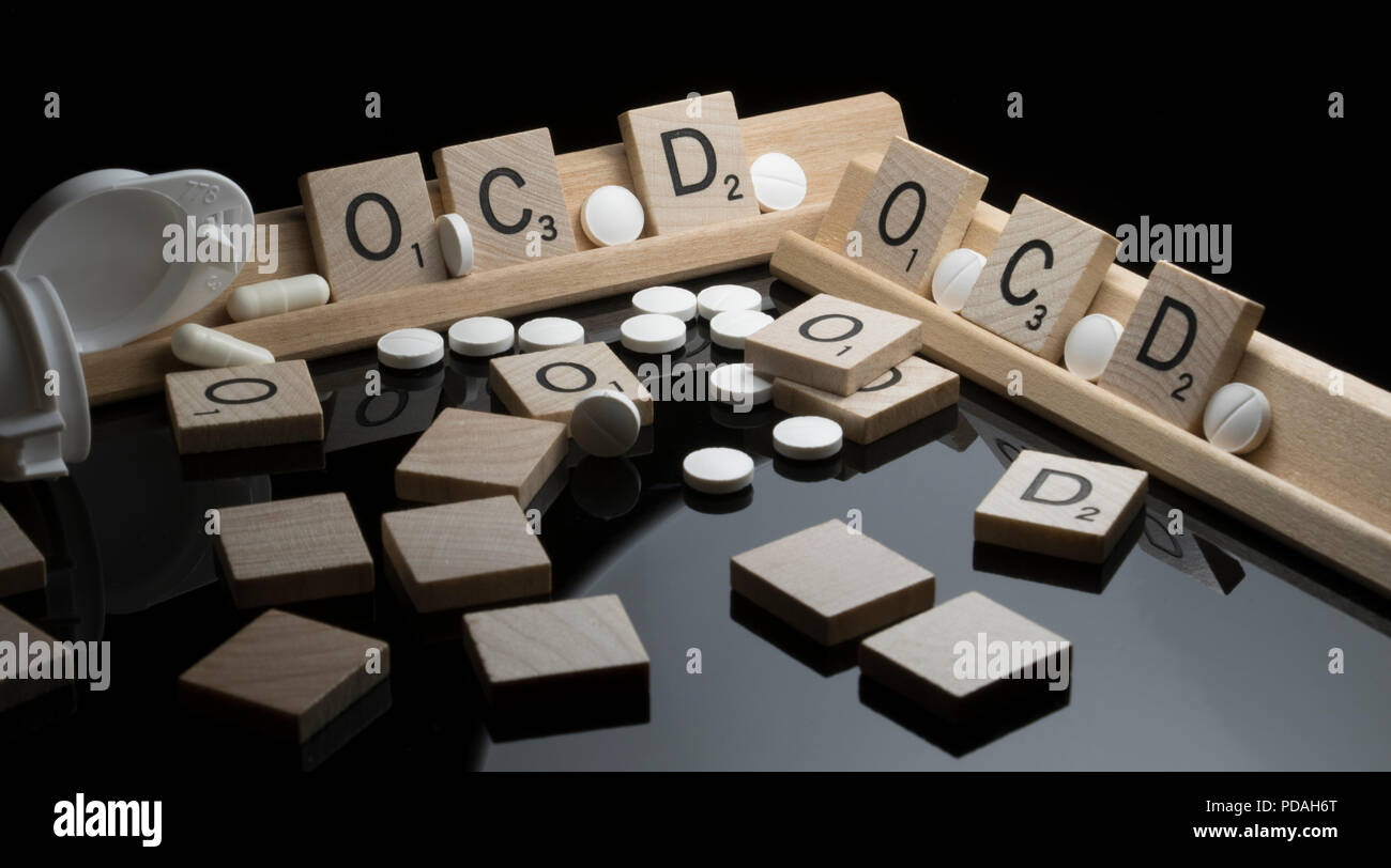 OCD and behavioral health management concept with block letter text and prescription pills. - Stock Image