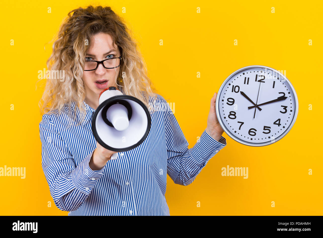 Woman in shirt with clocks and loudspeaker - Stock Image
