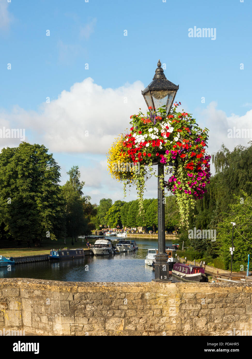 Boats moored on the river Thames at Abingdon Oxfordshire  seen from the river bridge with old lamp post and floral hanging baskets - Stock Image