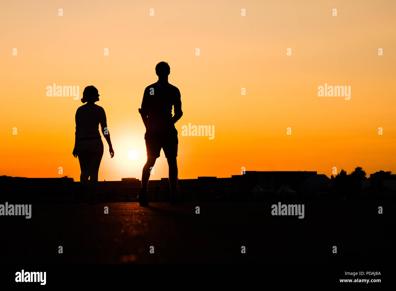 Silhouette Of Girl Looking Up To Boy On Sunset Sky Background Stock Photo Alamy