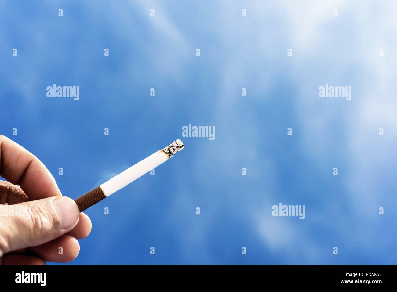 Single male hand holding a lit cigarette against a blue sky background with wisps of toxic smoke coming from the end of the cig. Copyspace area for ni Stock Photo