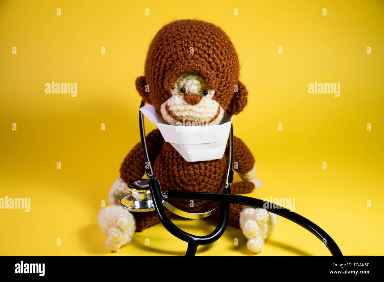 Medical Monkey stuffed toy panoramic. Cute plush brown monkey wearing a hospital mask and doctors stethoscope. - Stock Image