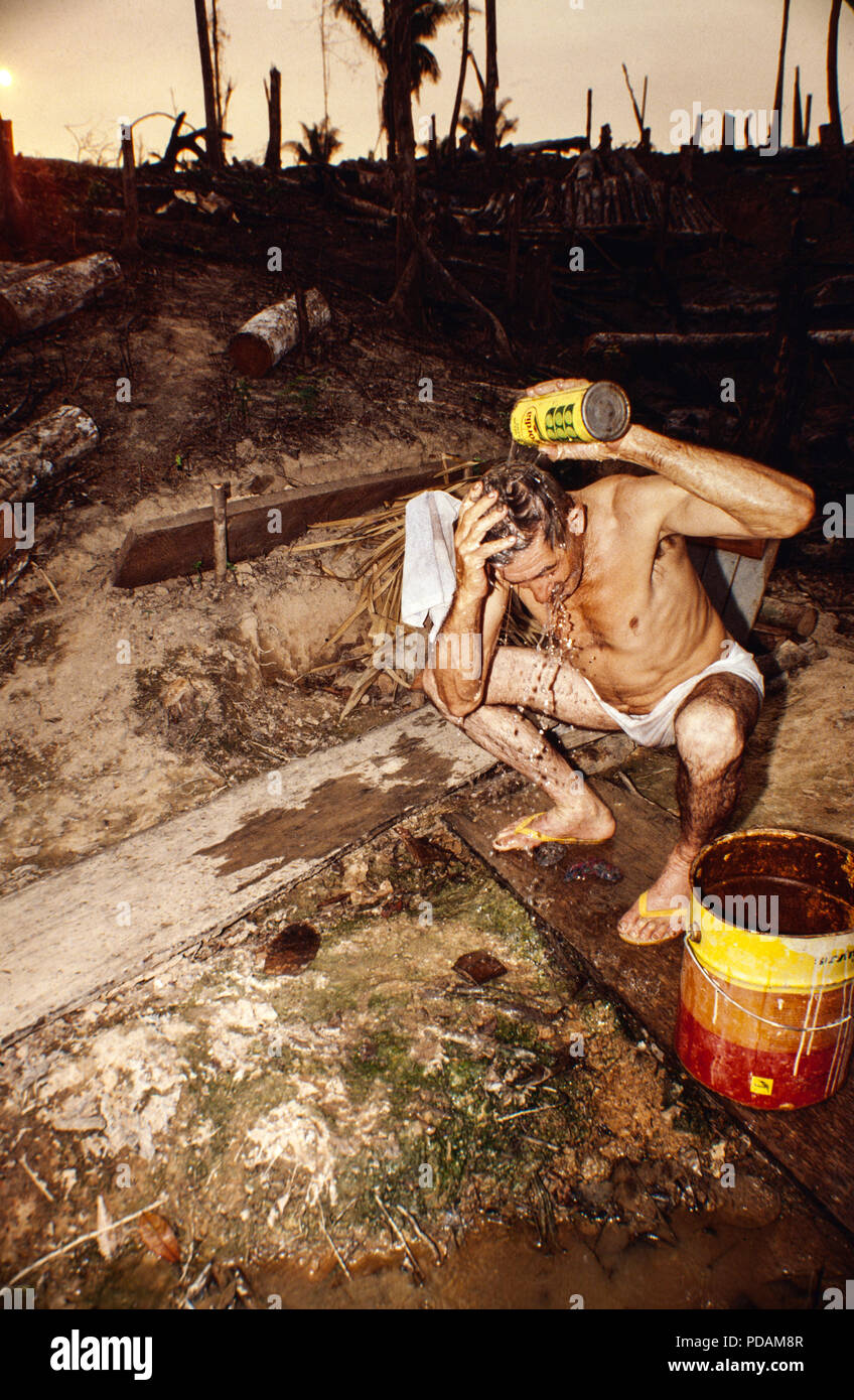Degrading labor, man washes himself using a can of water at the end of a tough working day clearing the forest, Amazon deforestation. Acre State, Brazil. - Stock Image