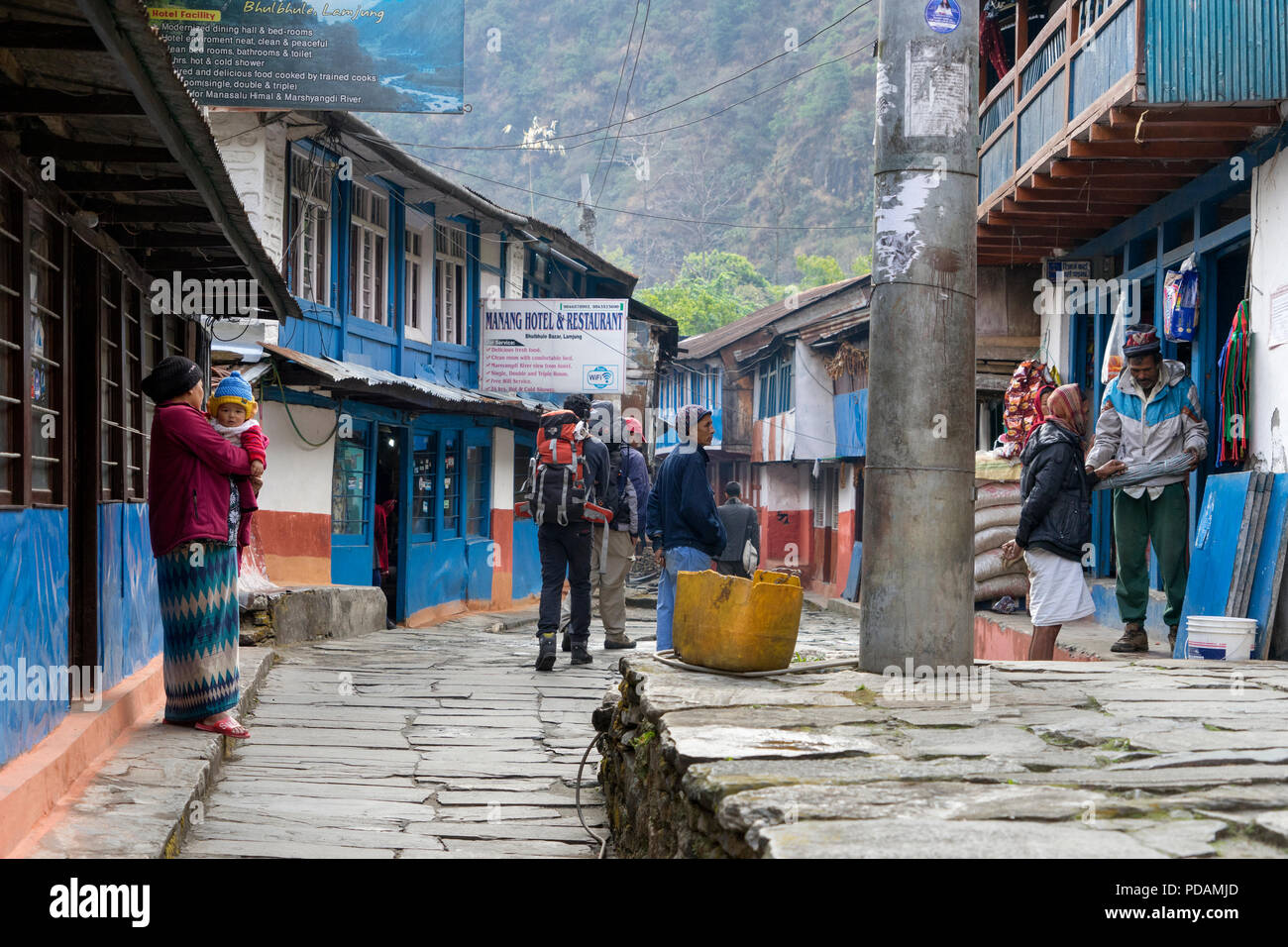 Local people and trekkers in the small village of Bhulbhule, at the start of the Annapurna Circuit, Nepal. - Stock Image