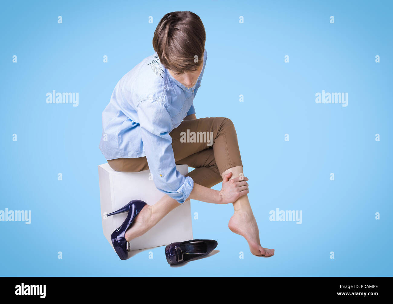 Young woman in high heels massaging her tired legs - Stock Image