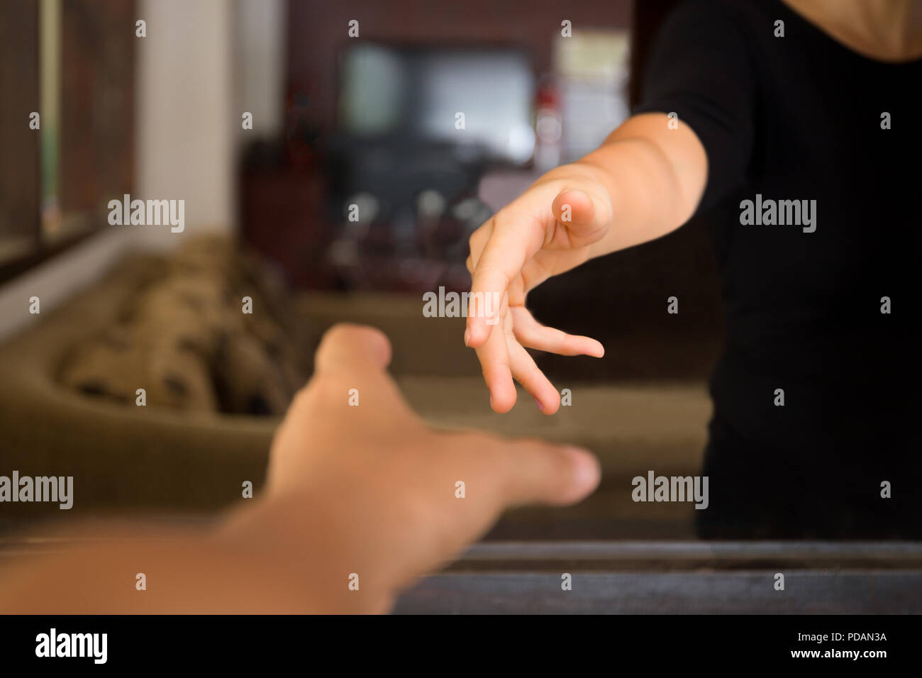 Male hands reaching out to help woman from inside. - Stock Image