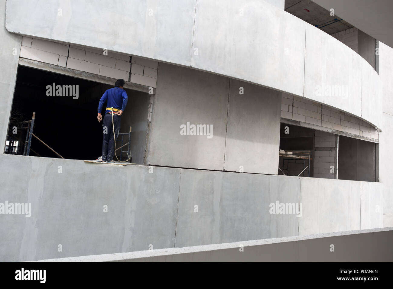 Builder with rope at high building in construction site. - Stock Image