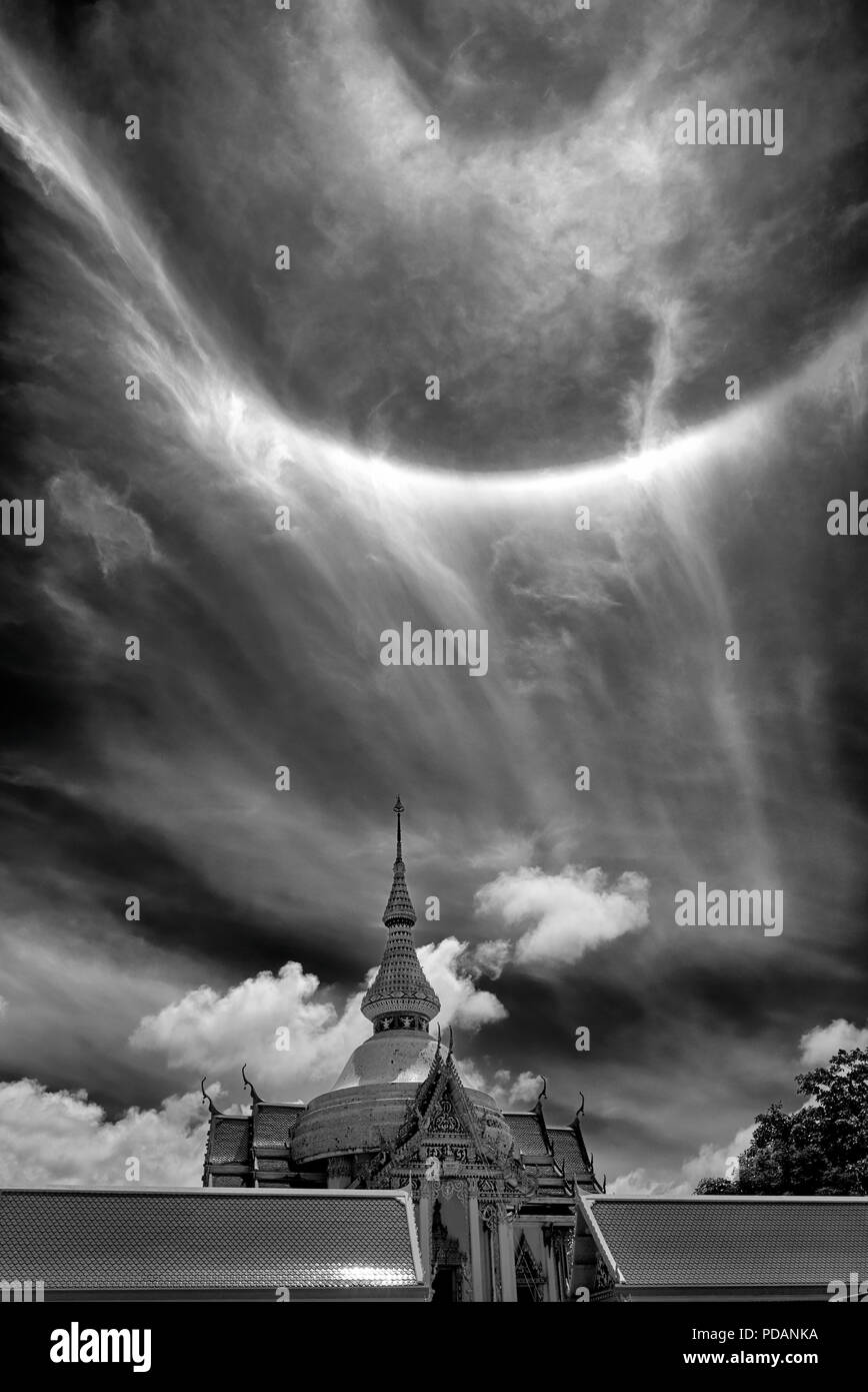 Sun Ring Phenomena 22° degree seen over a Thai Buddhist temple. Thailand Southeast Asia. Black and white photography dramatic sky monotone image - Stock Image