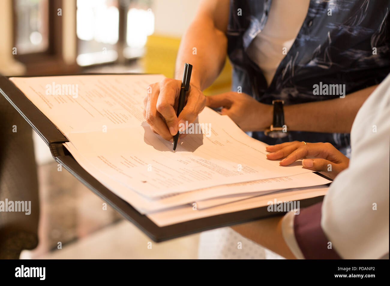 Man hand signing agreement from for hotel reservation. Stock Photo
