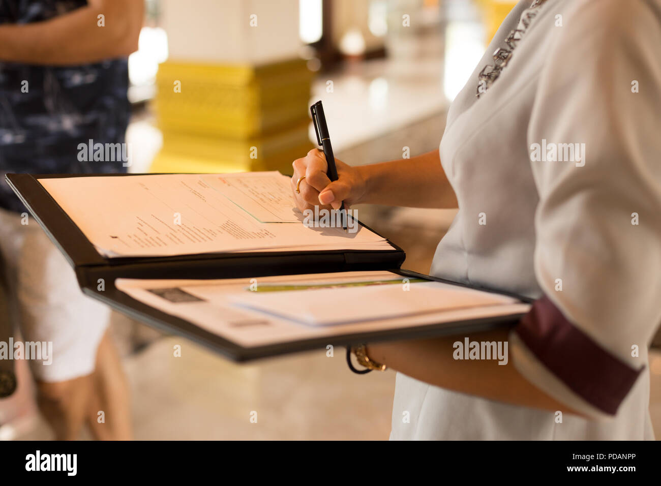 Receptionist filling in registration form at the hotel. - Stock Image
