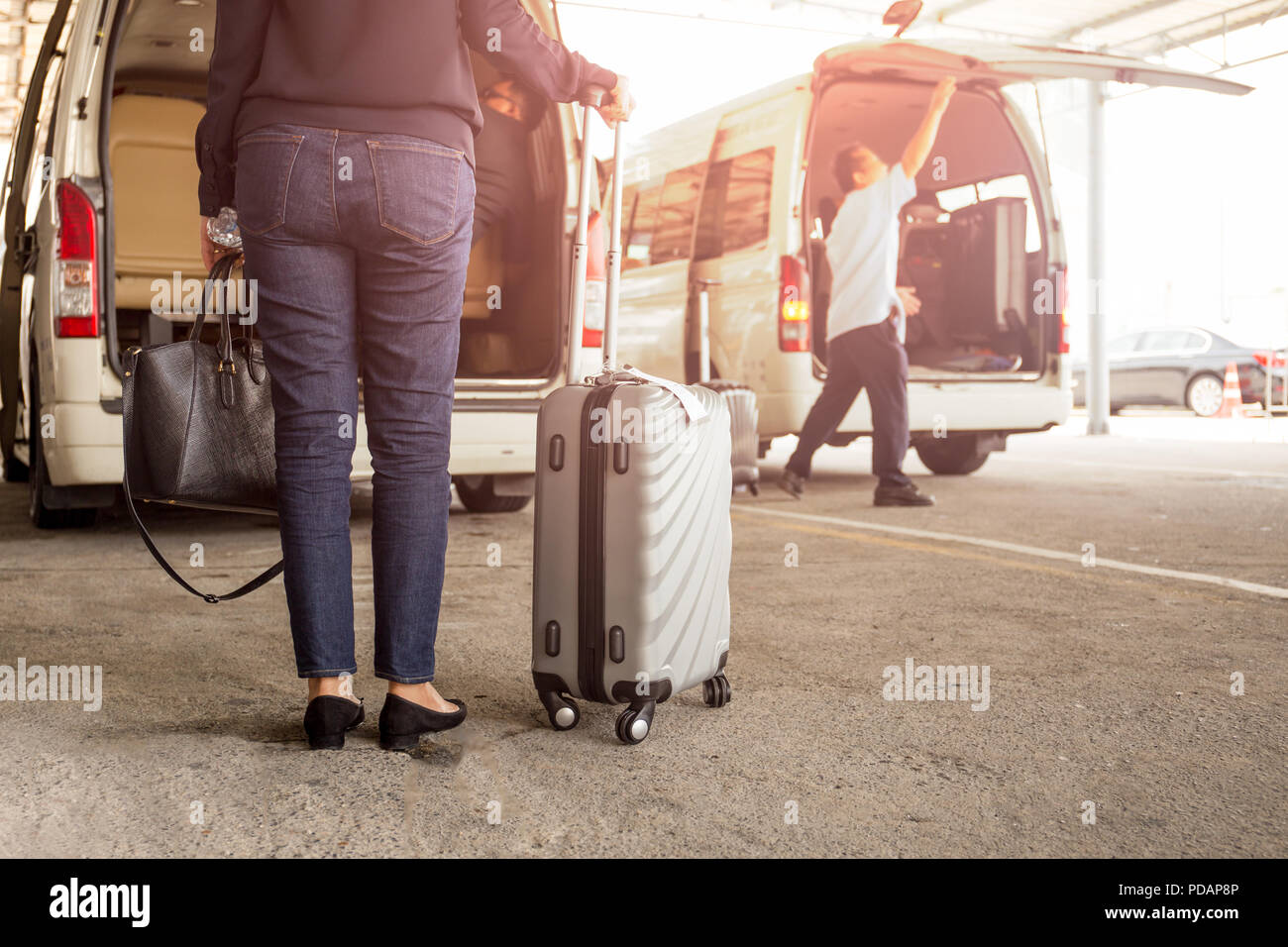 Woman tourist standing with luggage with pick up van at airport. - Stock Image