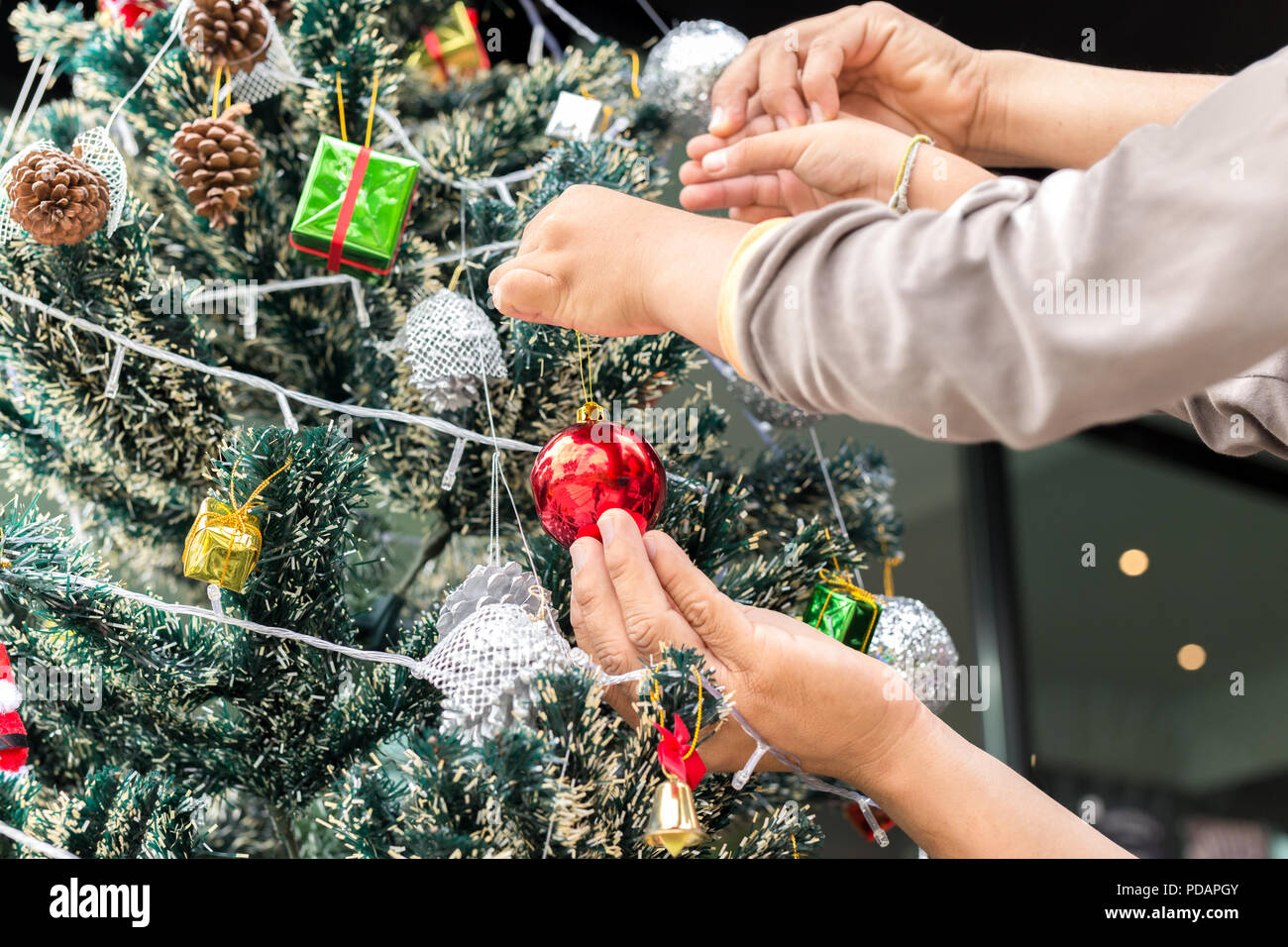Father and son decorating Christmas tree at home. - Stock Image