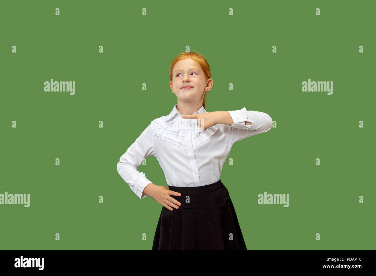 Happy teen girl standing, smiling and pointing isolated on trendy green studio background. Beautiful female half-length portrait. Human emotions, facial expression concept. - Stock Image