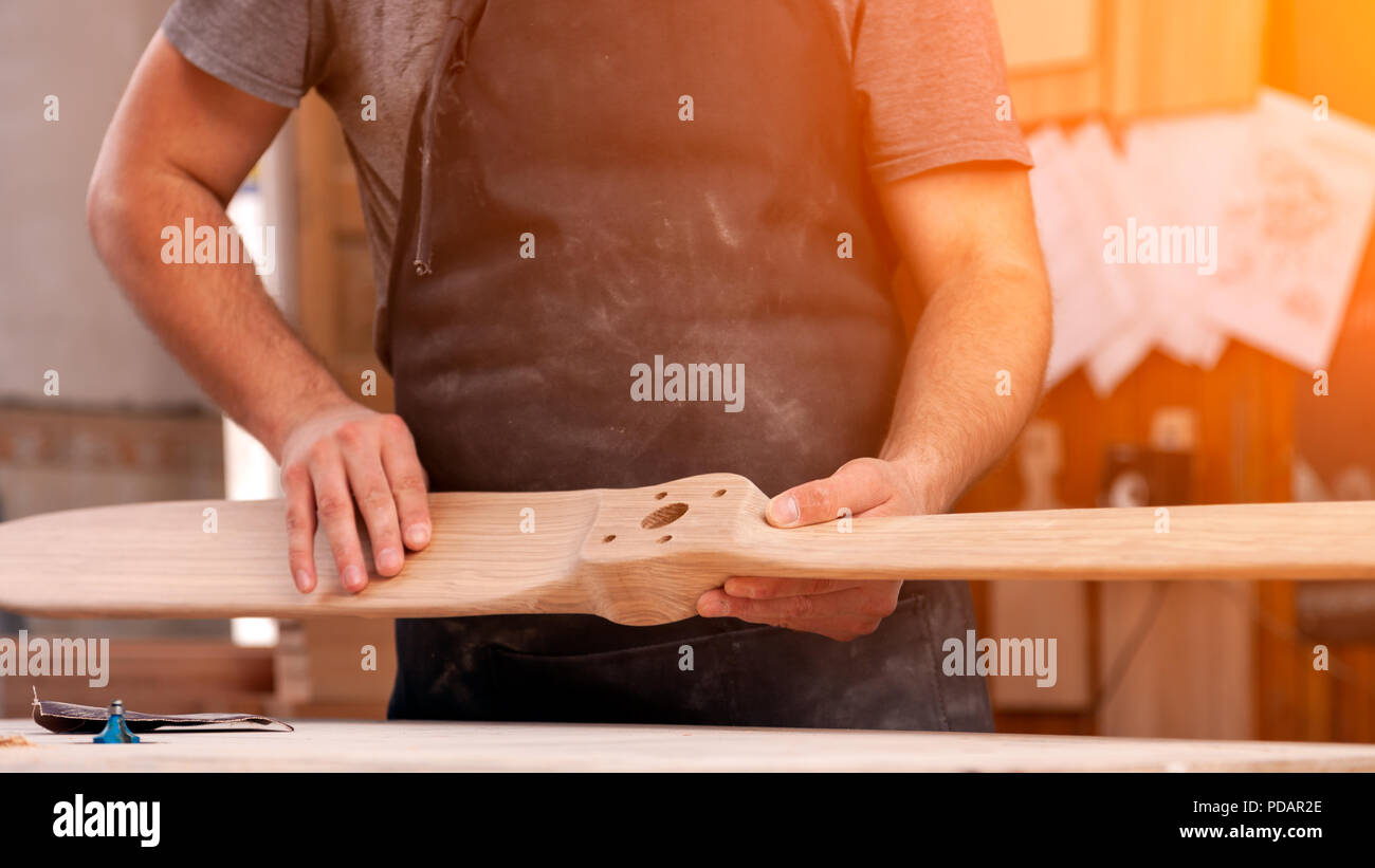 Experienced carpenter in work clothes and small buiness owner working in woodwork,  holding wood, on background  worktable in workshop Stock Photo