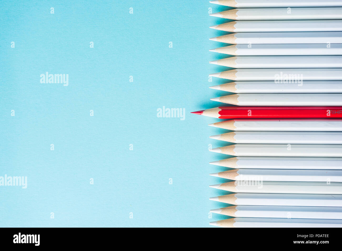 Business concept - lot of white pencils and color pencil on blue paper background. It's symbol of fight, leadership and communication. - Stock Image