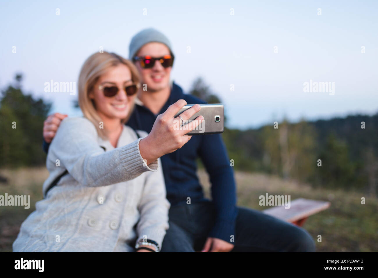 Young couple sitting on bench and taking selfie photo. Stock Photo