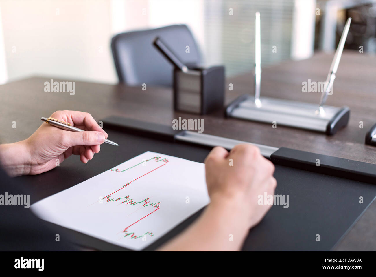 Man sitting at table and holds pen in left hand. There are sheet of paper with a trading chart on the table. Concept photo. - Stock Image