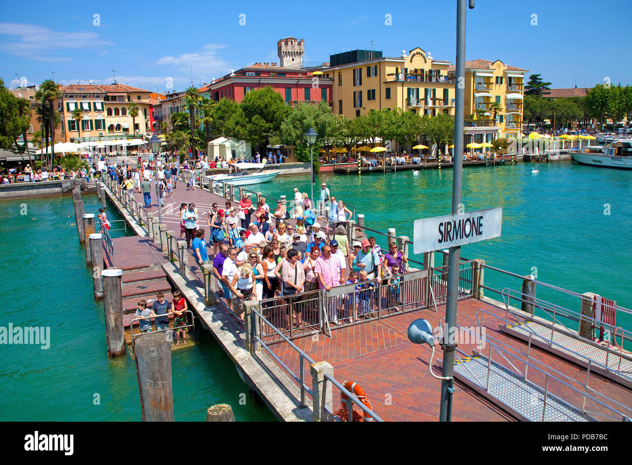 Tourists waiting on pier for the excursion boat, Sirmione, Lake Garda, Lombardy, Italy - Stock Image