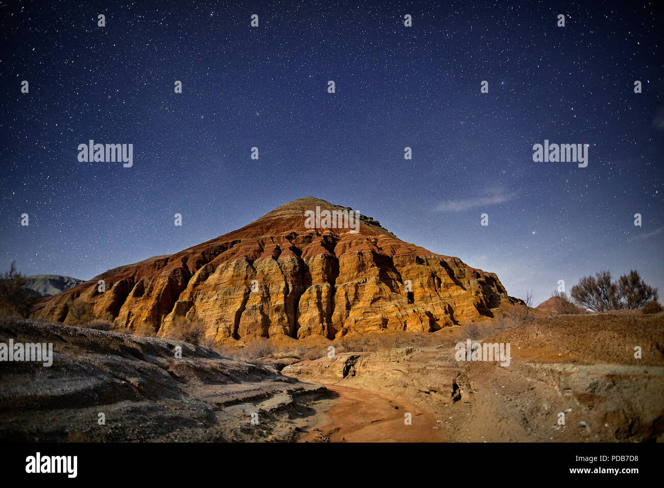 Red mountain of pyramid shape in the desert at night starry sky background. Astronomy photography of space and constellations. - Stock Image